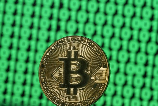 A token of the virtual currency Bitcoin is seen placed on a monitor that displays binary digits in this illustration picture, December 8, 2017. Picture taken December 8. REUTERS/Dado Ruvic/Illustration - RC1C7A3BB5E0