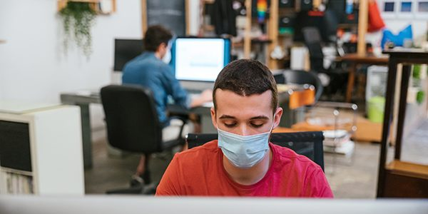 Millennials men with surgical mask at working at computer in off