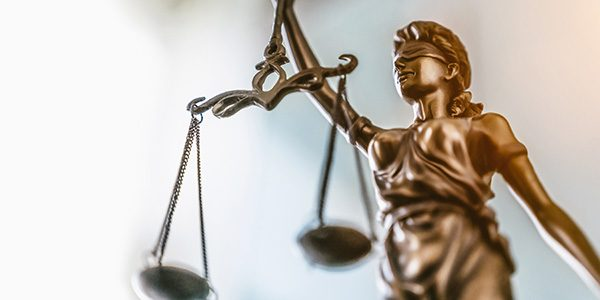 Statue of lady justice on bright background - Side view with cop