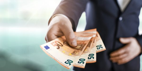 Business Man give a spread of euros cash over bank background. E