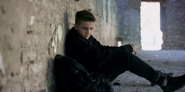 Teenager hiding from bullying in abandoned building, lonely, adolescent problems